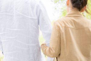 仲良さげに手を組む男女の後ろ姿、夫婦のイメージ画像。