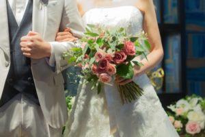 ブーケを持った花嫁とタキシードの新郎、結婚式のイメージ画像。