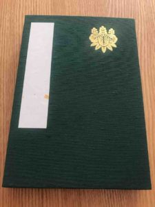 黄金色に輝く五七桐竹紋が記された、熱田神宮の御神印帳(御朱印帳)の表面。タイトルは書かれていない。