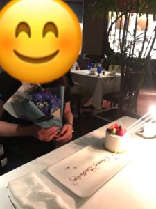 KAWABUNの誕生日ディナーの、サプライズで出されたメッセージ付きホールケーキと青い花束)