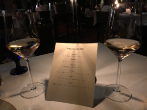 テーブルに置かれた誕生日ディナーのスペシャルコースのメニュー表とシャンパン