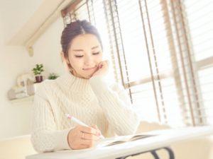 ノートを見つめて考える女性。