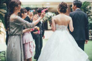 結婚式で笑顔でバブルシャワーを浴びる新郎新婦